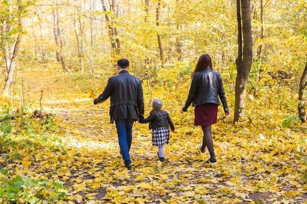 Концепция осень, природа и семья - семья гуляет в осеннем парке, вид сзади