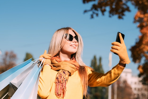 Fall park walk stylish lady with shopping bags taking selfie on smartphone