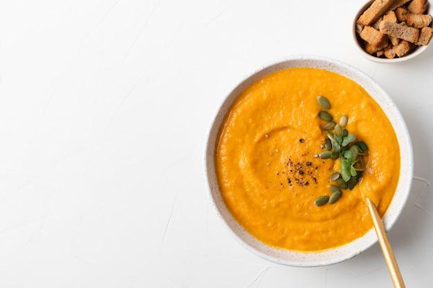 Осенний тыквенный суп с кремовым гарниром из микрозелени на белом пространстве с копией пространства