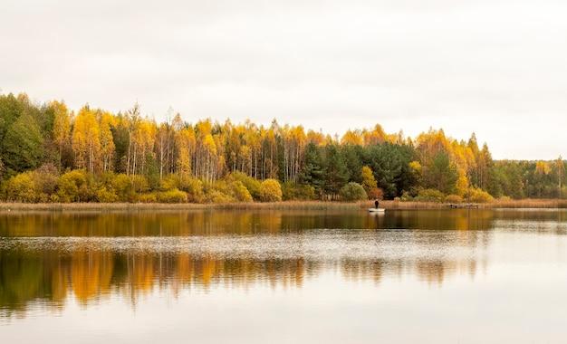 화려한 가을 숲이나 숲과 호수에 반사 된 아름다운 풍경을 가을. 보트에있는 남자
