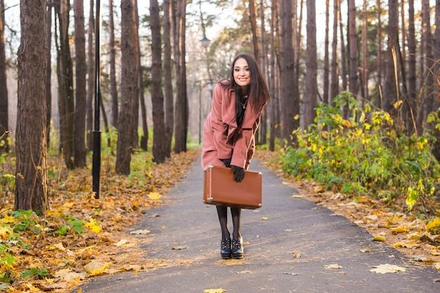 가을, 계절과 사람들이 개념-가을 공원에서 여자 가방과 함께 포즈