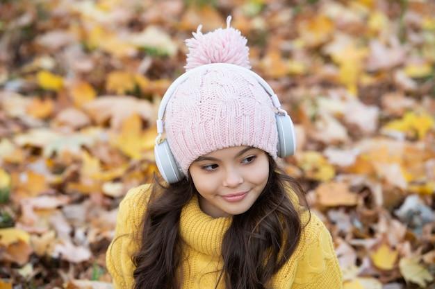 秋のファッション。秋の帽子の十代の少女の肖像画は背景を残します。笑顔の子供は屋外のヘッドフォンで音楽を聴きます。秋の自然。 9月。学校に戻る。自然の美。