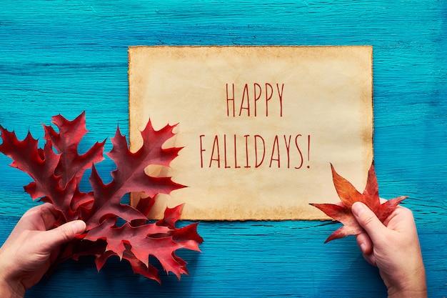 Осенняя сезонная квартира лежала на бирюзовом дереве. женские руки держат красный дуб и кленовые листья. текст счастливых осенних праздников на старом пергаменте.