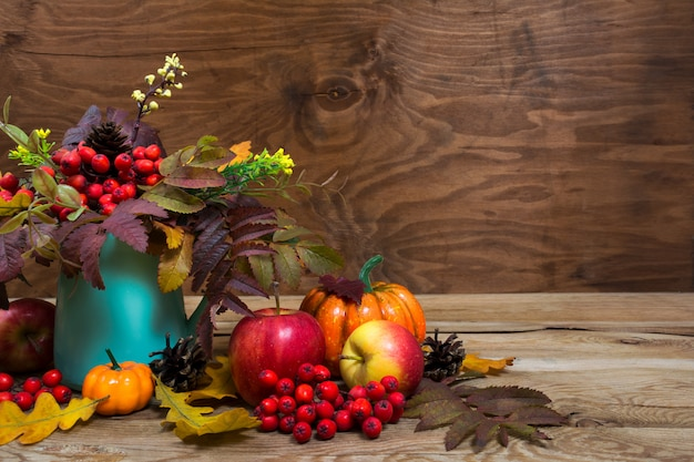Fall table centerpiece with rowan berries, leaves in turquoise vase, copyspace