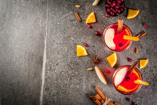 Fall and winter cold drinks, cranberry and orange holiday christmas punch with cinnamon, anise stars,  on black background copy space top view