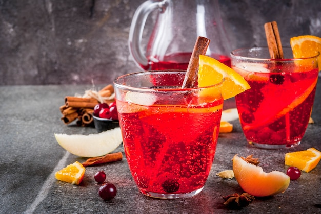 Fall and winter cold drinks, cranberry and orange holiday christmas punch with cinnamon, anise stars,  on black background copy space