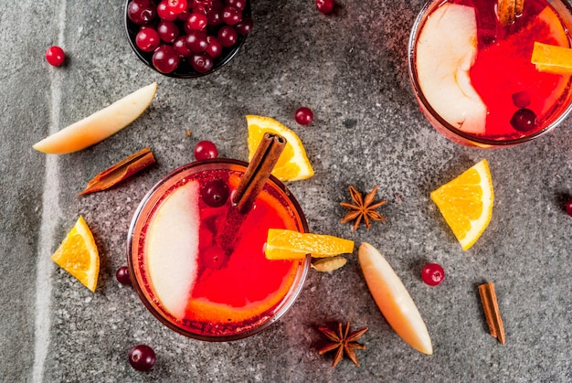Fall and winter cold drinks, cranberry and orange holiday christmas punch with cinnamon, anise stars,  on black  copyspace top view