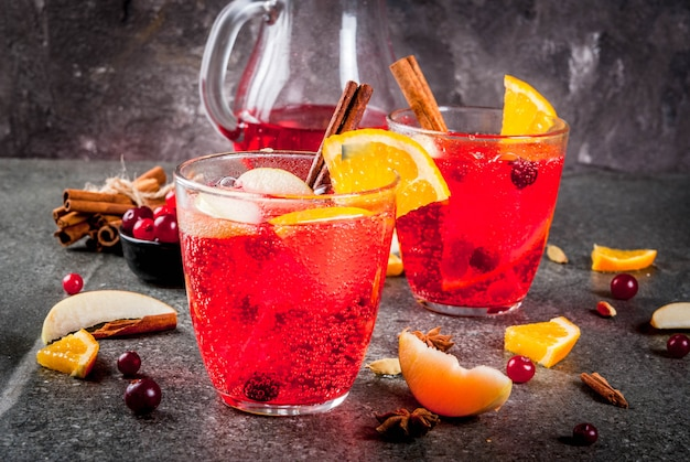 Fall and winter cold drinks, cranberry and orange holiday christmas punch with cinnamon, anise stars,  on black  copyspace