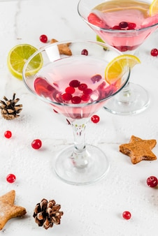 Fall and winter drinks. christmas holiday beverage. festive cranberry martini with lime. on white table with christmas decoration, copy space