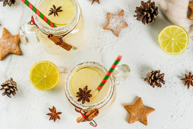 Fall and winter drinks. christmas holiday beverage. festive snowball cocktail with lime juice, cinnamon, liqueur, sugar and anise stars. on white table with christmas decoration, copyspace top view