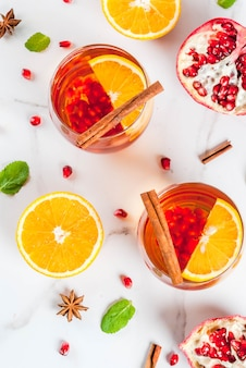 Fall and winter drinks. warm refreshing cocktail with  pomegranate, oranges, cinnamon, spices and mint. on a white marble table.   top view