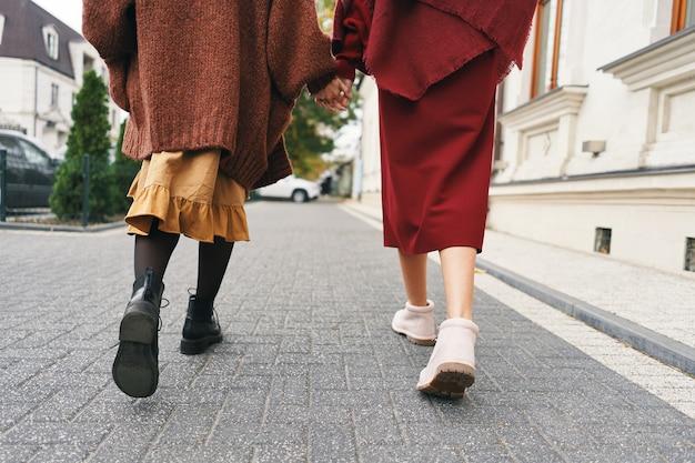 秋冬のファッション衣装の詳細。街の通りを歩いている2人のスタイリッシュな女の子の背面図のトリミングされた画像。ウールの服、靴、アクセサリーのセット。