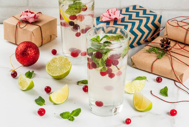 Fall and winter refreshment drink cranberry mojito cocktail with lime and mint with christmas gifts and decorations on white table