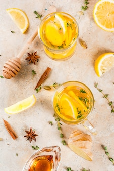 Fall and winter traditional drinks. warming hot tea with lemon, ginger, spices (anise, cinnamon) and herbs (thyme) top view