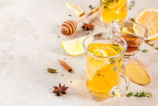 Fall and winter traditional drinks. warming hot tea with lemon, ginger, spices (anise, cinnamon) and herbs (thyme)