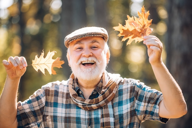 Fallen autumn leaves strewn about the ground elderly man smiling outdoors in nature grandfather havi...