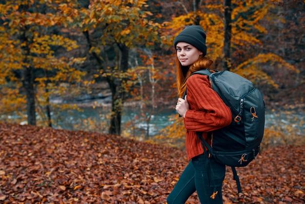 秋の公園で落ち葉とバックパックで女性観光客を背景に川