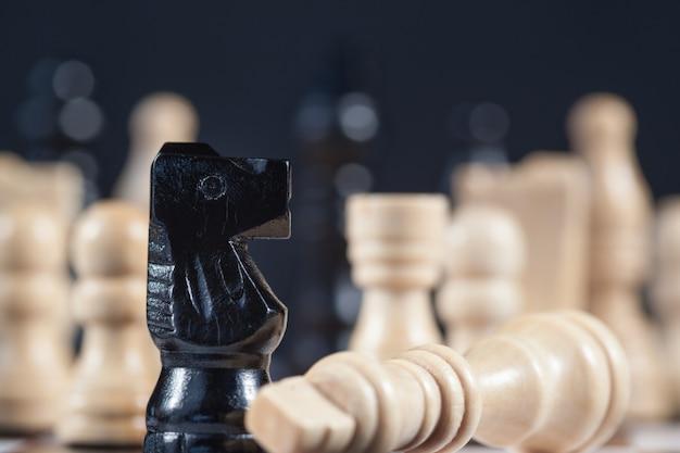 Fallen white chess piece lying next to black knight