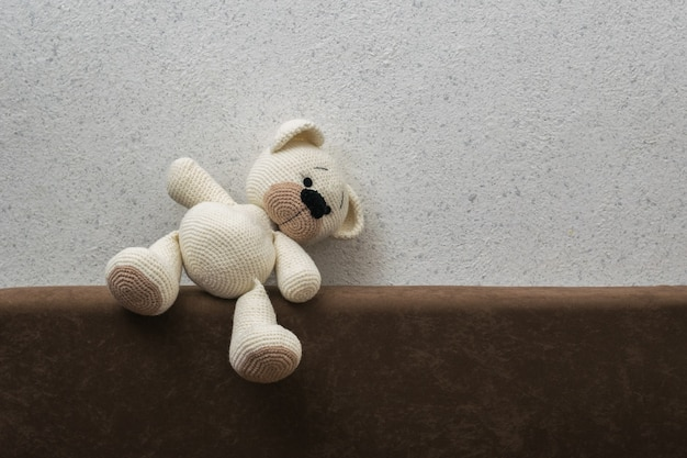 A fallen white knitted bear cub on a sofa against a light wall. beautiful knitted toy.