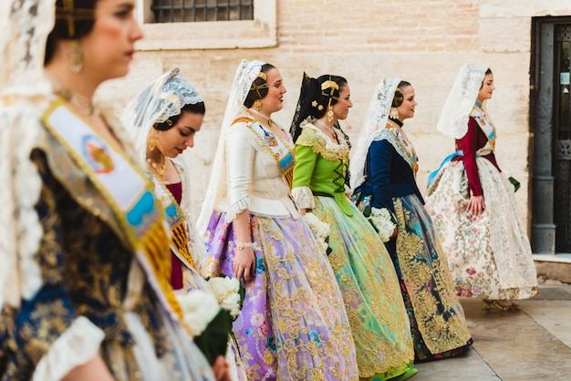 Falleras women about to offer their bouquets to the virgin during the fallas offering event.