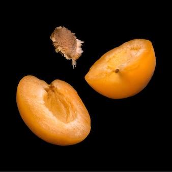 Падающие абрикосы, изолированные на черной поверхности. летящие фрукты в воздухе.