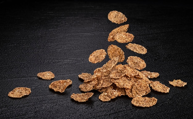 Falling bran flakes on black table, pile of traditional breakfast cereal