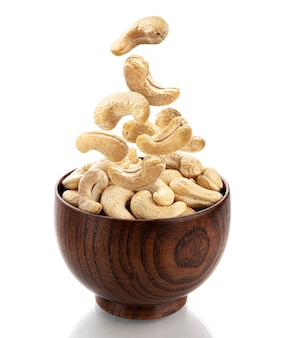 Falling cashew nuts into wooden bowl isolated on white background with clipping path