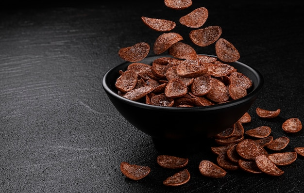 Falling chocolate corn flakes on black background, healthy cereal breakfast