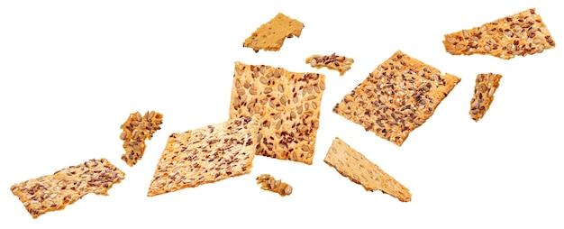 Падающий хрустящий хлеб с кунжутом, льном и зернами подсолнечника, изолированные на белом фоне с обтравочным контуром
