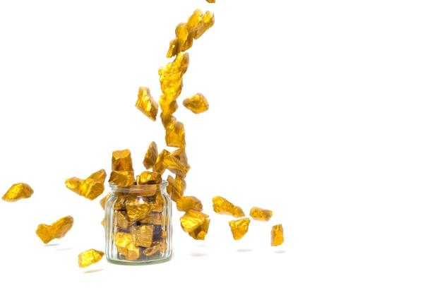Падающие золотые самородки и стеклянная банка изолированы