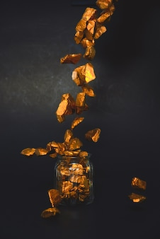Falling gold nuggets, gold ore and glass jar