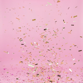 Falling golden confetti on pink background