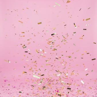 Падение золотой конфетти на розовом фоне
