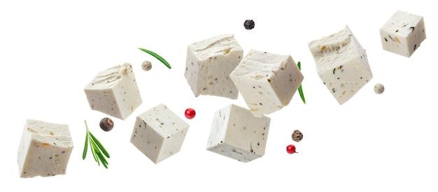 ハーブとスパイス、白い背景で隔離のさいの目に切った柔らかいチーズと落ちるギリシャのフェタチーズキューブ
