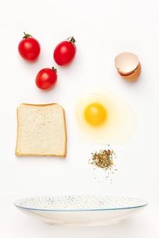 The falling ingredients of fried egg. healthy breakfast ingredients.