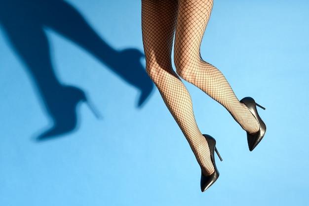 セクシーな黒い網タイツとエレガントなハイヒールを身に着けている女性の落ちてくる足