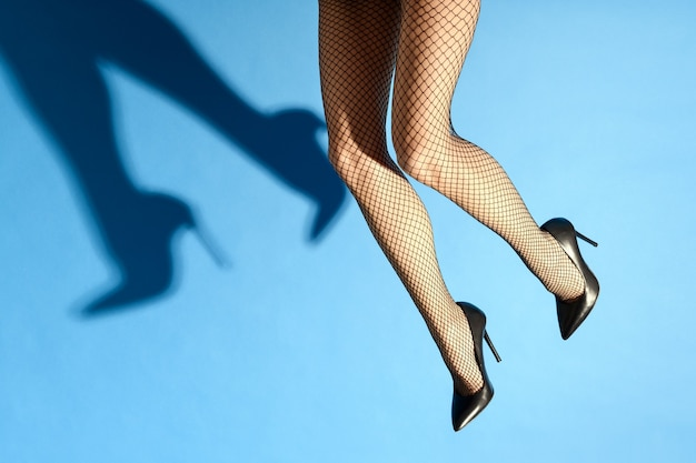 Falling legs of a woman wearing sexy black fishnets and elegant stilettos