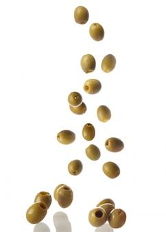 Falling olives on white surface