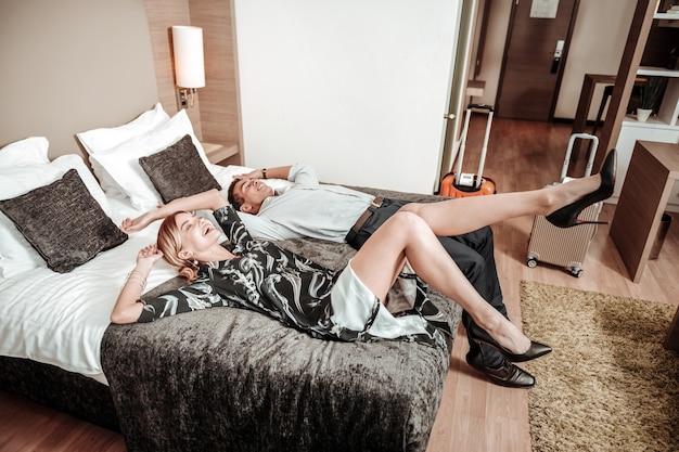 Падение на кровать. счастливая красивая влюбленная пара падает на кровать в отеле после долгого и утомительного полета