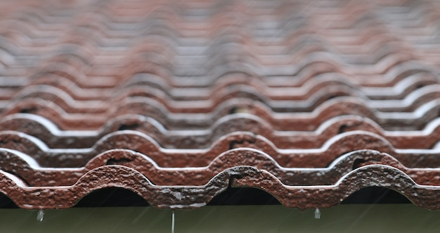 Falling rain drop on brown brick roof