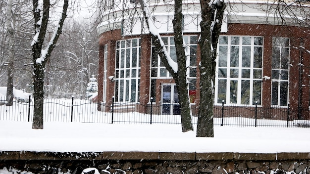 Падает снег в городе. бизнес-центр во время метели. снежная буря в городе. городской пейзаж с падающим снегом.