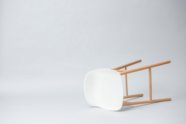 Falling tall white bar stool legs are wood on gray background