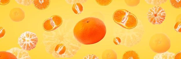 落下するみかん、黄色の背景の上にみかんを浮揚させる、パノラマ画像