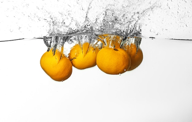 Falling of tangerines into water on white