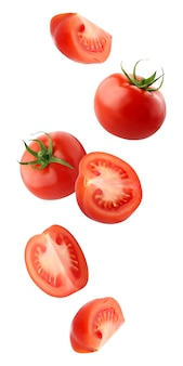 クリッピングパスで白い背景に分離された落下トマト。丸ごと赤いトマトとカットピースが空を飛んでいます。野菜が落ちる。