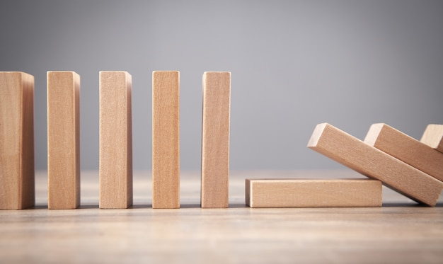 Falling wooden domino. business. crisis. risk