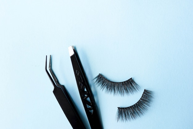 False eye lashes, black tweezers on blue background with copy space.