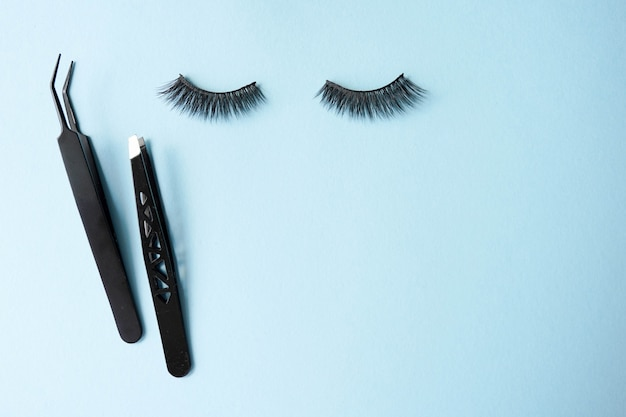 False eye lashes, black tweezers on blue background with copyspace