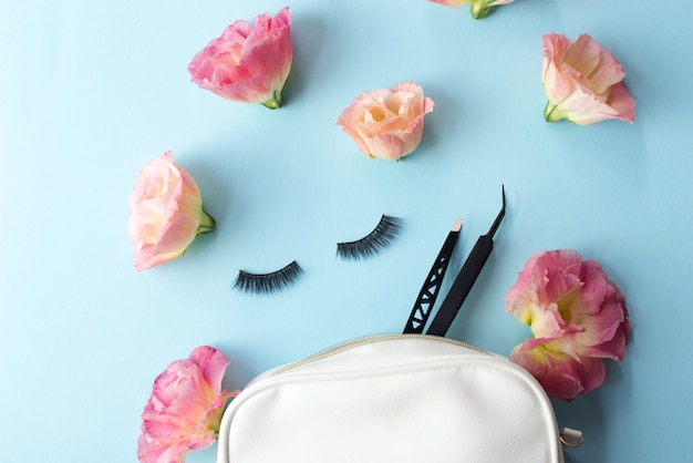 False eye lashes, black tweezers and pink flowers on blue.