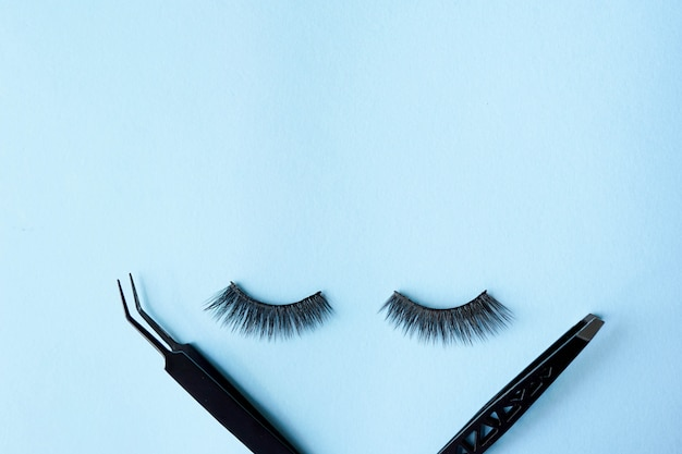 False eye lashes with two black tweezers on blue background with copy space